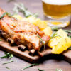 baked pork ribs with potatoes, rosemary and a glass of beer